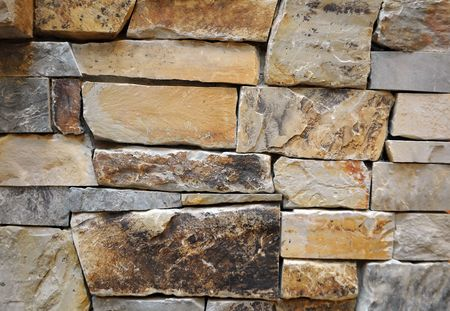 Close up of a stone wall texture. Yellow and brown Imagens