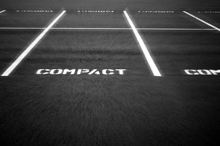 zooming: Compact parking lot with a slight zoom effect applied zooming in toward the word COMPACT.
