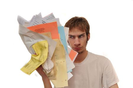 contained: Angry young man ripping holding up an overload of paperwork. Nothing copyrighting is contained in the papers Stock Photo