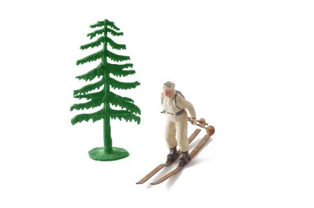 Miniature tree and skier isolated on white. photo