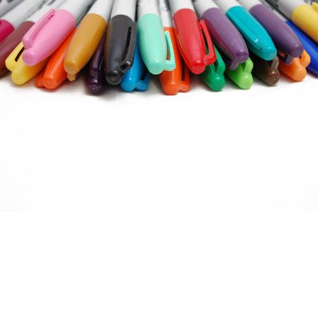 desgn: A bunch of markers on the edge of a white background.