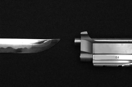 A black and white image of a sword and pistol pointing at each other on a black cloth. Stok Fotoğraf - 6046002