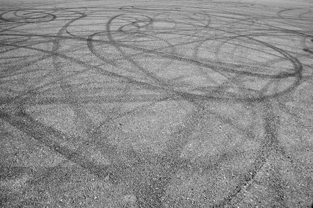 tyre tread: A bunch of random skid marks from cars in an empty asphalt parking lot. Lots of random ones.
