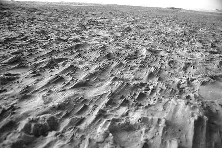 Black and white. Rocky, rough, sandy ground.