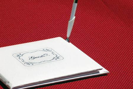 Closed white guestbook that says Guests on the front, with a pen standing up on its side. It is on a red table cloth. photo