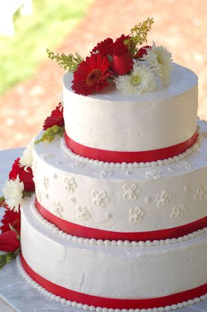 Wedding cake with red stripes and flowers photo