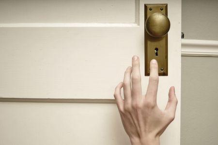 Pale hand reaching for golden brown doorknob.