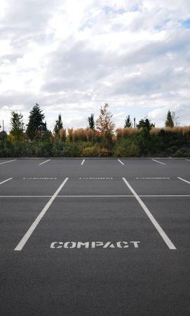 Verticale foto van een parkeer terrein met het woord COMPRIMEREN in alle ruimten met bomen en lucht ruim in de achtergrond.