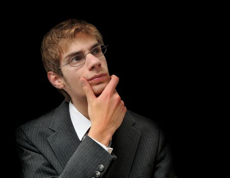 Young white male Caucasian man in suit seriously ponders and questions himself isolated on black background.