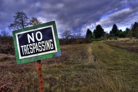 NO TRESPASSING sign in front grass rural country driveway field Stock Photo