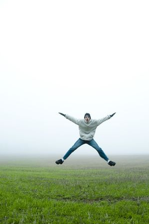 jacks: a teenager boy does excited jumping jacks in a green grass field