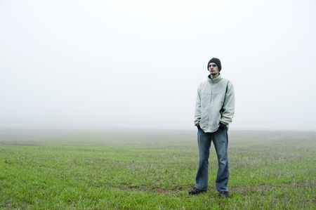White caucasian teenager stands in a green grass field with a black beanie and white jacket on with his hands in his blue jeans. He is looking towards the camera with a blank expression. There is white fog behind him for copyspace. photo