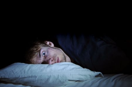 turmoil: White male caucasian young adult on bed with head on pillow with eyes wide open staring off into space at the camera. Afraid of the dark. Stock Photo