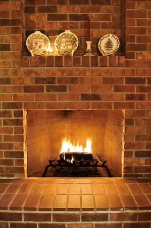 stone fireplace: Simple clean brick fireplace with a single fire log burning out to give heat. There are Christmas plates decorating it at the top, but those can be cropped out to remove any holiday type theme.