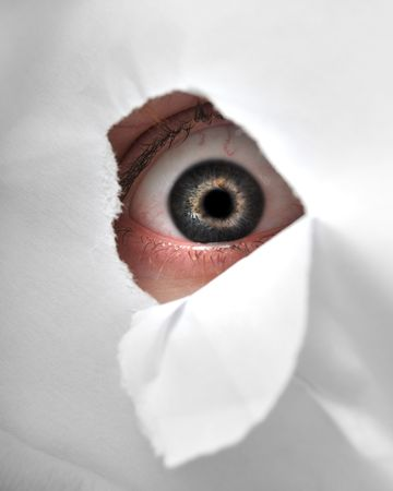 A man peaking through a peice of paper to be a spy. Stock Photo - 6154263