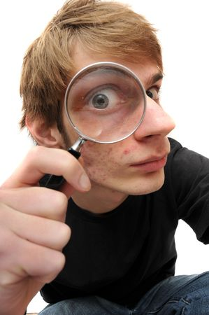 closely: A young adult man looking down  with a magnifying glass up to his eye, searching for just the right clue to crack the case of the mystery.