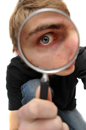 clue: A young adult man looking down  with a magnifying glass up to his eye, searching for just the right clue to crack the case of the mystery.
