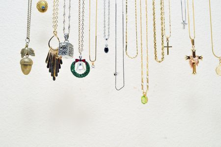 A bunch of various metal necklaces hanging up against a white wall.