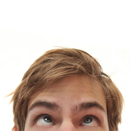Young adult man staring up with cross eyes into empty white isolated copy space Stock Photo - 6154252