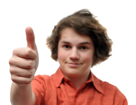 purposely: A young teenager holding his thumb up with a smile. His hand is in focus but his body is purposely blurred. Stock Photo