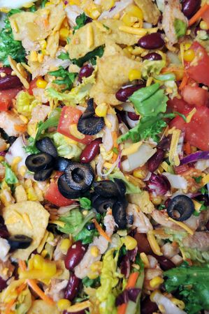 Delicious taco salad closeup. Contains black olives, green lettuce, red tomatoes, yellow cheddar cheese, purple kidney beans, white tender chicken, yellow corn and orange carrot shavings. photo