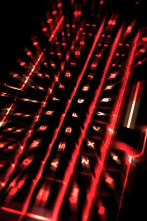 backlit keyboard: A backlit illuminated computer keyboard with red for the color and a zoom effect.