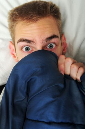 aghast: white Caucasian young adult teenage man hides under his blankets and covers because he is scared of the spooky things that go bump in the night.