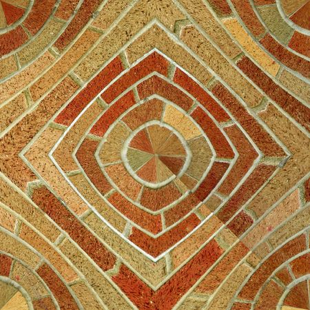 A circular brick pattern background texture of red and brown bricks that makes a seamless pattern when mirrored.