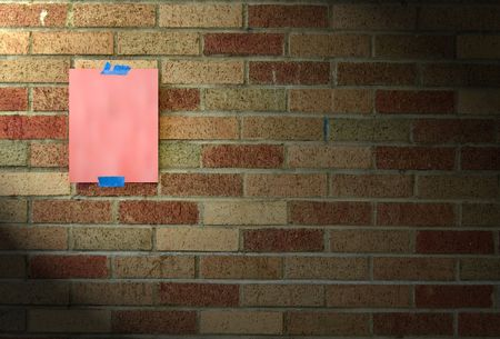 taped: A blank piece of hot pink paper taped to a brick wall with blue tape.