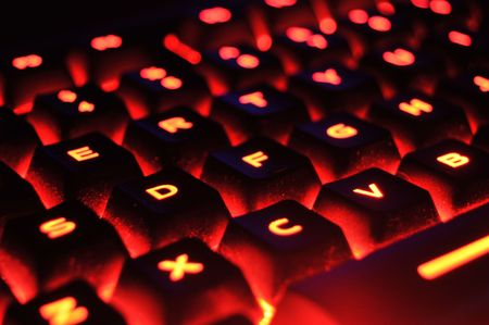 An abstract closeup of a red illuminated backlit glowing computer keyboard Reklamní fotografie