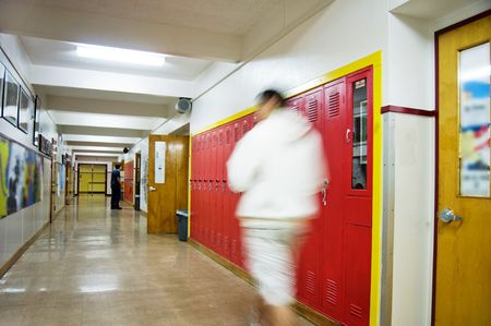 An empty highschool hallway with a person walking down it with red lockers on the right side.. Stock Photo - 6295245