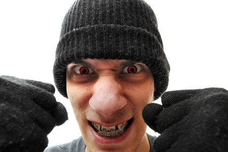 stickup: A young troubled bandit criminal robber thief with a black beanie and black gloves, isolated on white background, holding his fists up to the camera. He has red eyes to make him look evil. Stock Photo