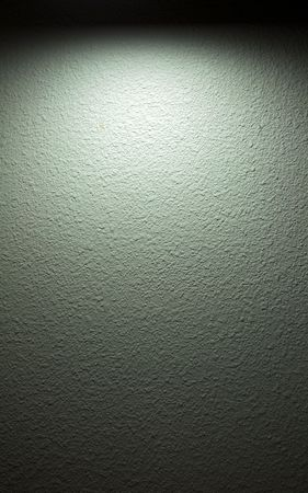 A spotlight shines on a painted textured wall. It has a slight green tone to it.