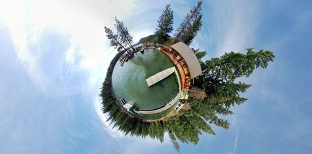 projected: A 360x180 panoramic image projected to be in stereographic form. This is a pond with a dock, with trees and blue sky.
