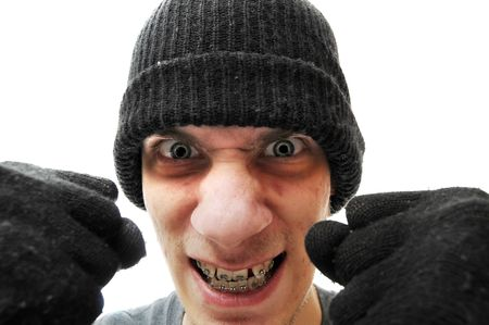 stealer: A young troubled bandit criminal robber thief with a black beanie and black gloves, isolated on white background, holding his fists up to the camera.  Stock Photo