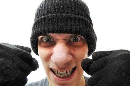 hijacker: Un bandido agitada joven ladr�n criminales ladr�n con un beanie negra y guantes negros, aislados sobre fondo blanco, sosteniendo sus pu�os hasta la c�mara.  Foto de archivo