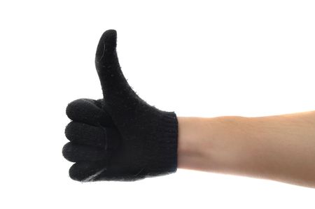 unambiguous: Black glove on a white hand with thumbs up isolated on white background. Stock Photo