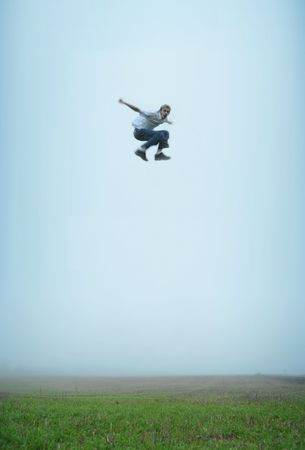 twitch: A man makes a massive jump in an empty field. He is flying in mid air! Stock Photo