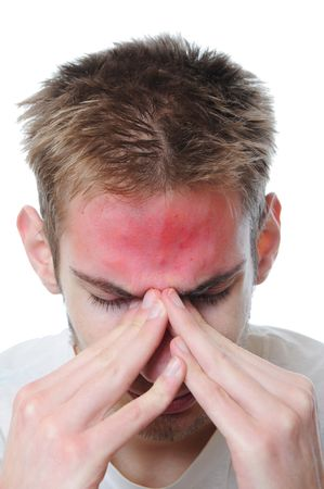 Young adult man stressed. He rubs his eyes in pain. Isolated on white background. The red spot on his forehead represents his pain. photo