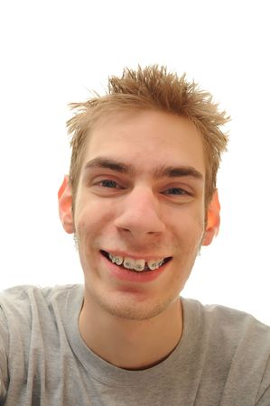 Young adult teenage man laughs over white background. He has his braces on for his teeth photo