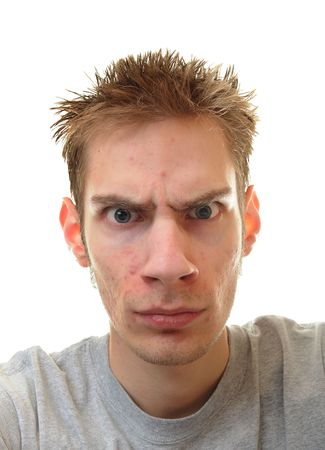 unemotional: Young man furrowing his eyebrow with a blank intense stare. Stock Photo