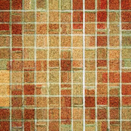 A square brick tile background made from red, brown, and tan square bricks. photo