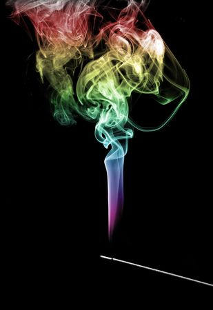 Smoke coming up from an incense stick over a black background photo