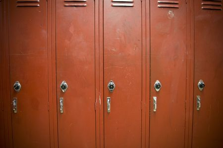 corridors: A row of worn down old red lockers. The lockers look old and worn down.