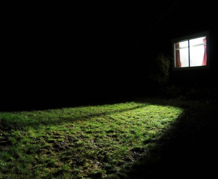 awaken: A dark house at night with a window with a light on in the room spilling out light onto the grass lawn yard