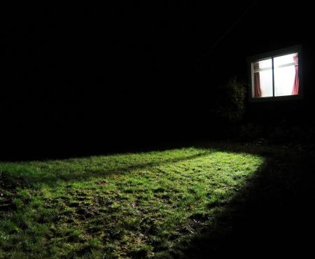 Een donkere huis bij nacht met een venster met een licht op in de kamer morsen uit licht op het gras gazon yard