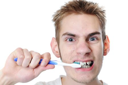 Young adult man brushes teeth isolated on white. He has braces. Stock Photo - 6614698