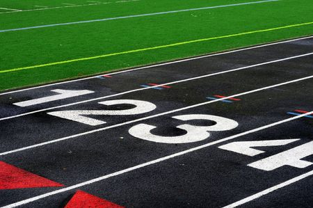 mile: Numbered lanes on a mile running fitness athletic black track.