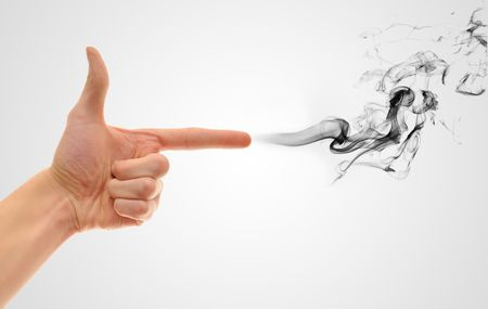A hand making a shape of a pointed hand gun on white gradient background with black smoke coming out of the finger