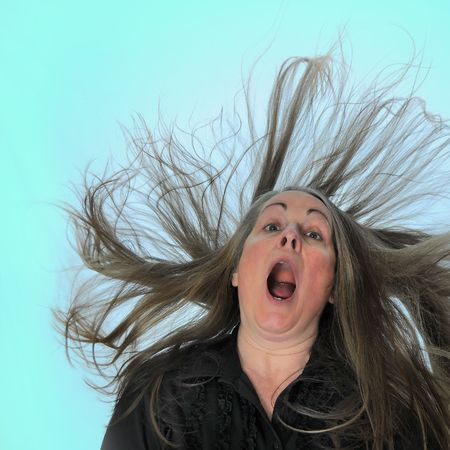 wind blown hair: A woman screaming in front of a blue background with her hair blasting behind her. Stock Photo